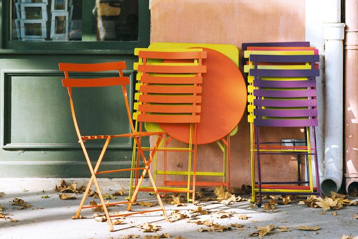 Tables et chaises Fermob de différentes couleurs, pliées, et rangées contre un mur