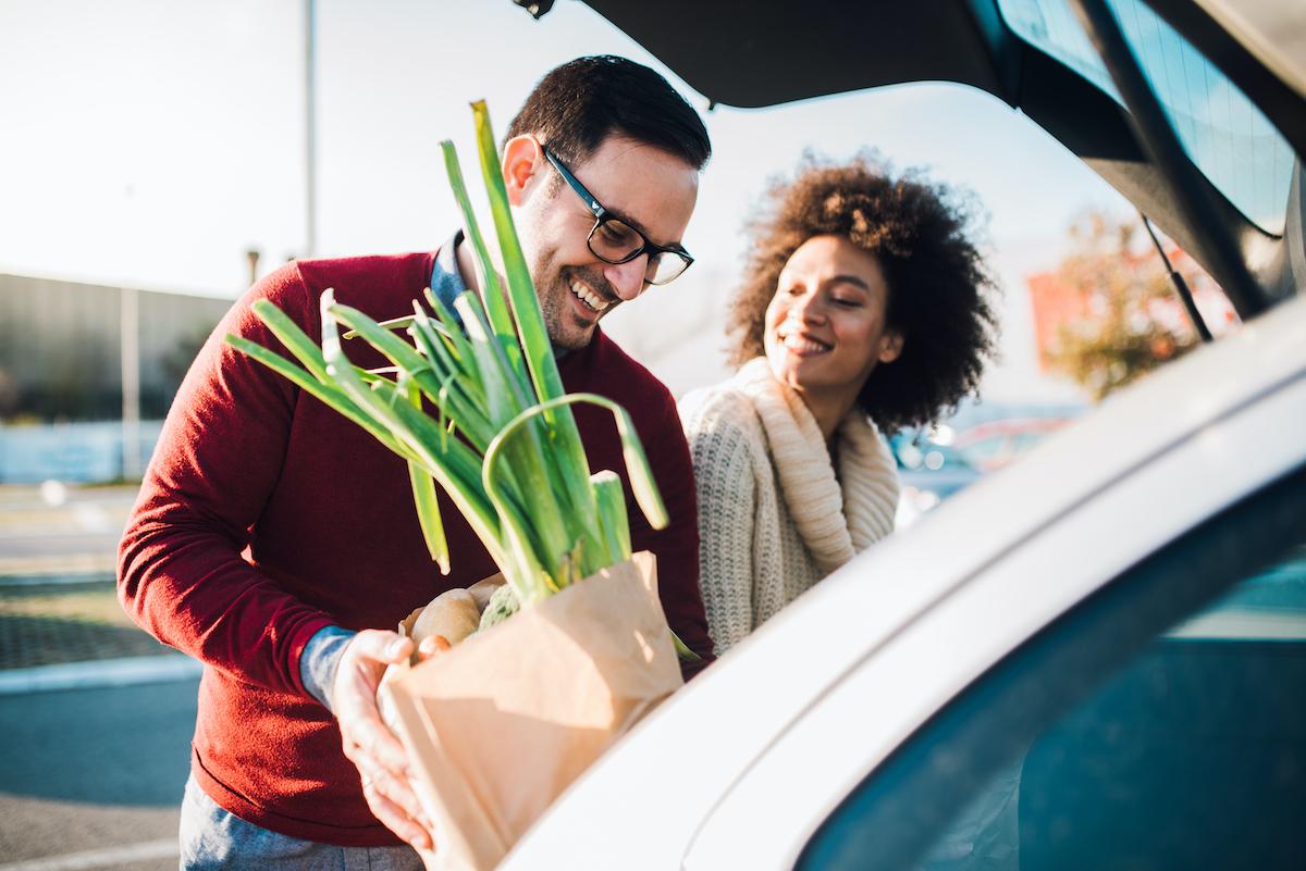 Un couple souriant chargeant ses courses dans un coffre de voiture