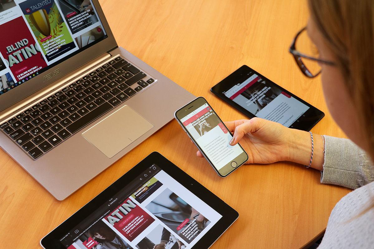 Une personne qui teste un site web sur ordinateur + tablette + 2 smartphones