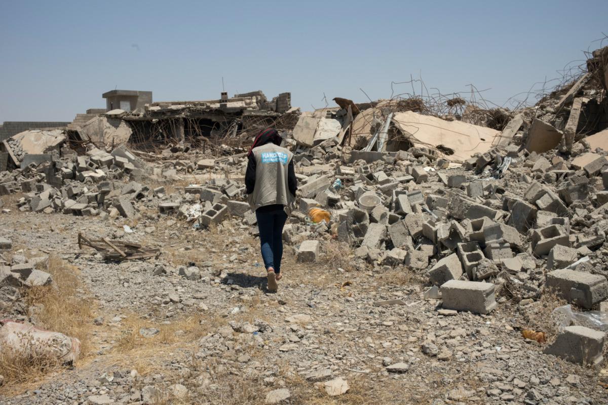 un homme de Handicap International marchant au milieu des décombres dans une ville bombardée en Irak
