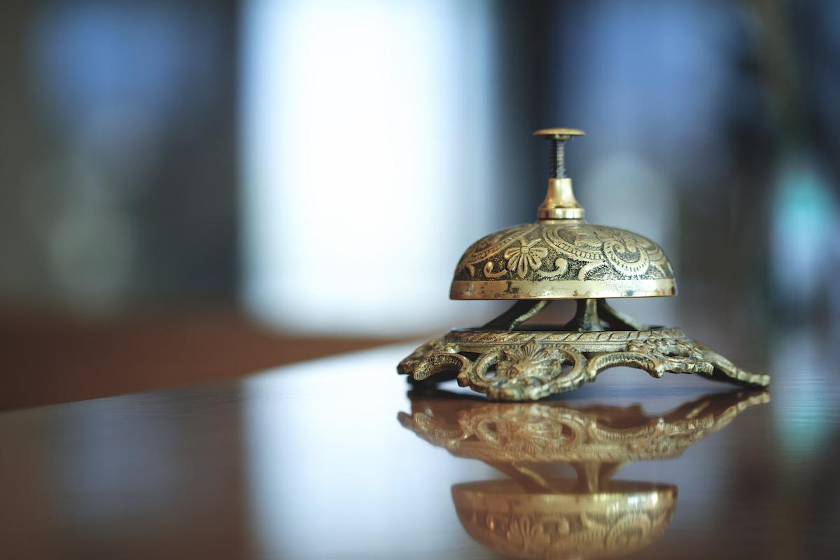 Photo illustration hôtellerie de luxe - sonnette dorée sur comptoir accueil hôtel