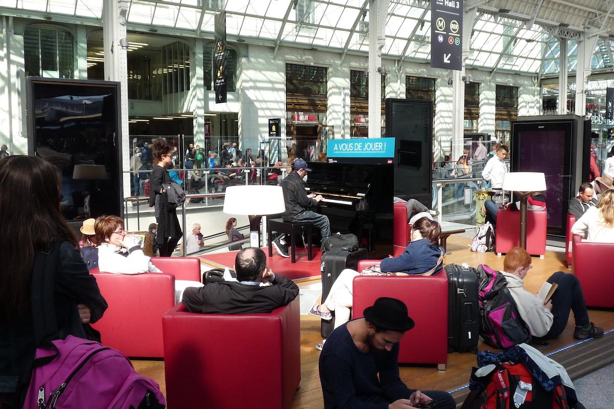 Joueur de piano à Paris Gare de Lyon, au milieu de passagers en salle d'attente