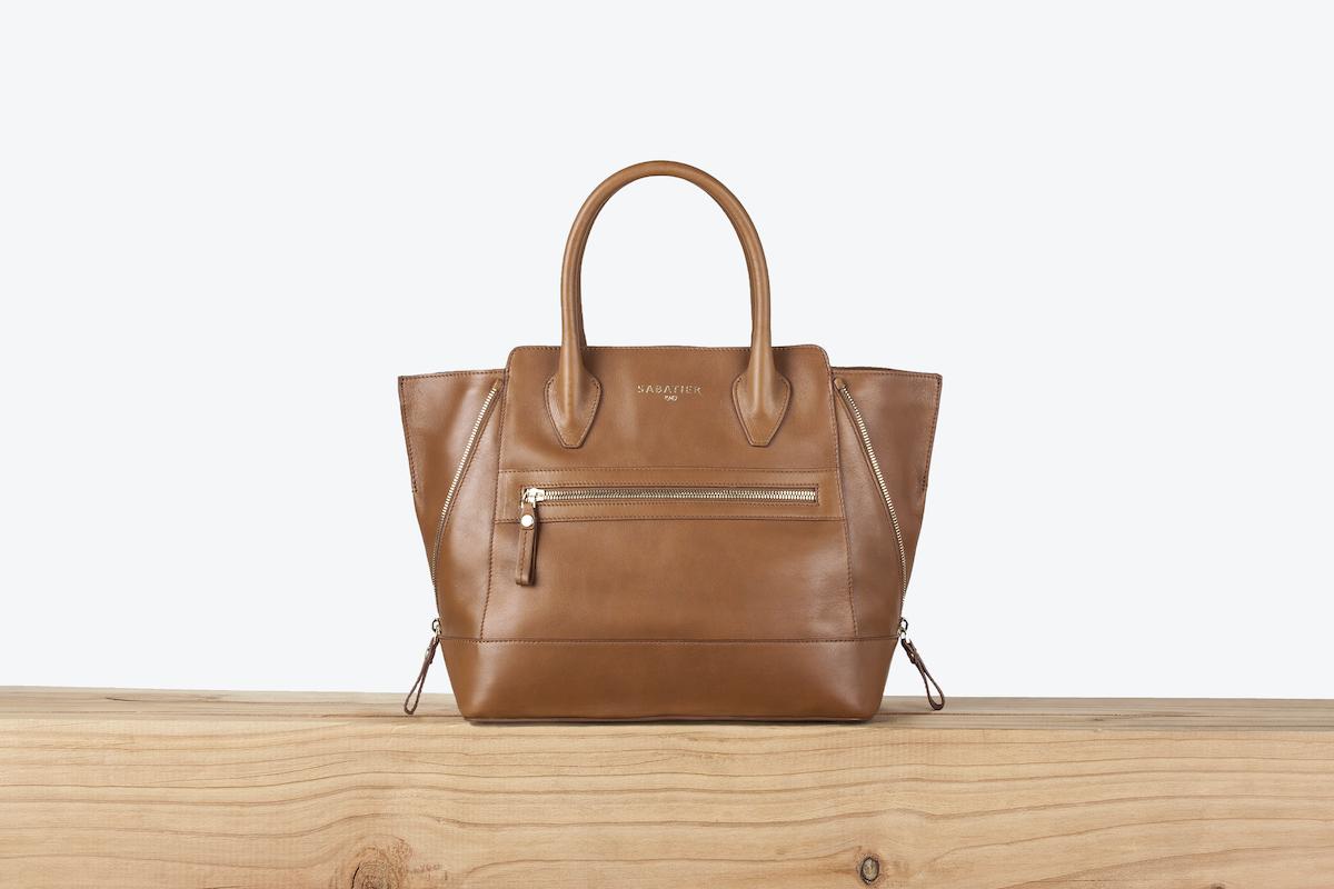 Un sac à main marron posé sur une surface en bois clair