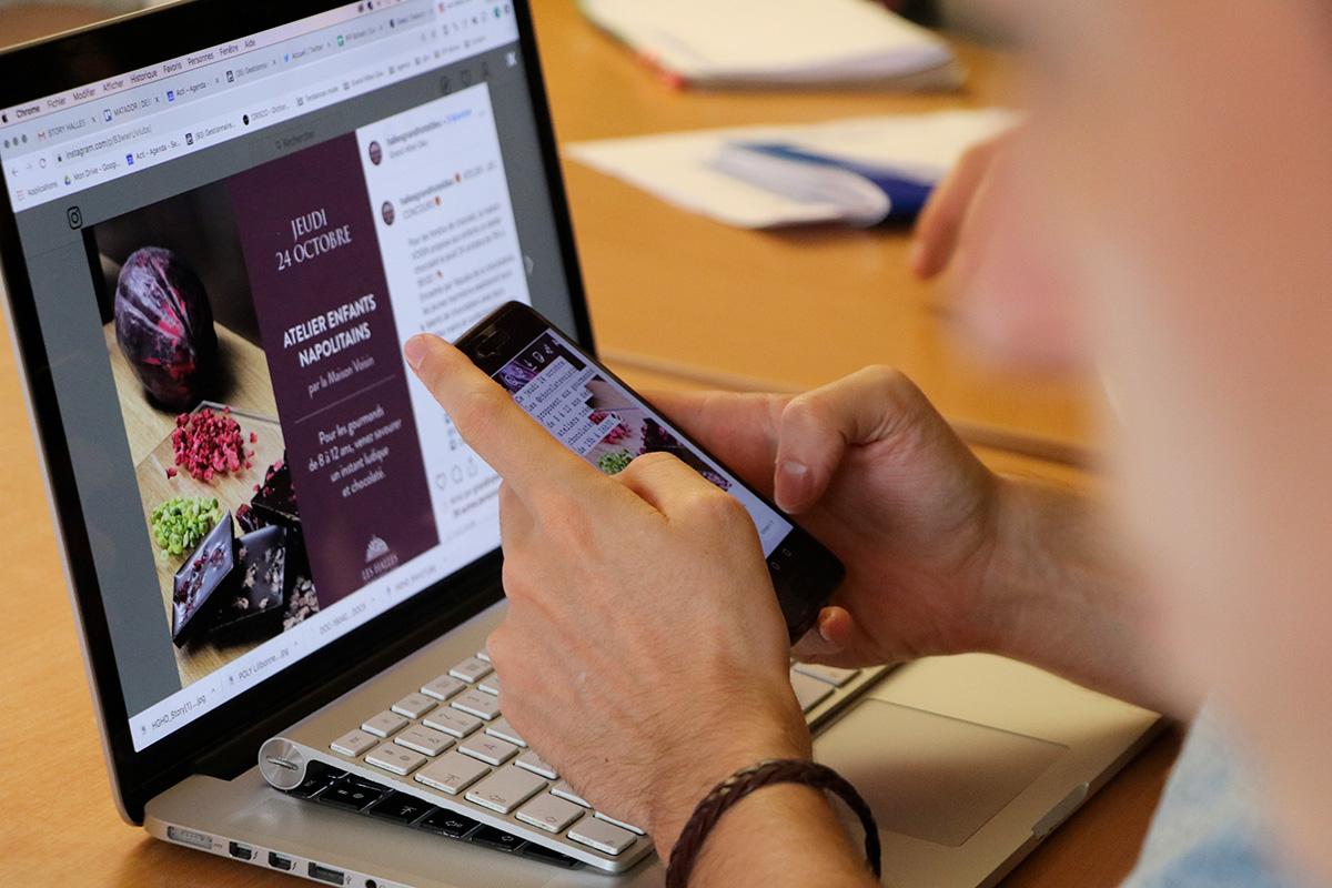Un consultant Social Media d'acti utilisant son smartphone et son ordinateur portable